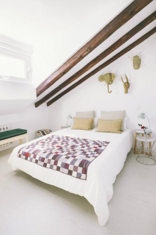 Authentieke houten balken in een lichte slaapkamer
