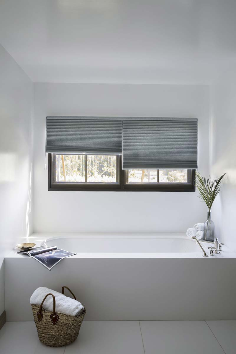 grijze plissegordijnen witte badkamer
