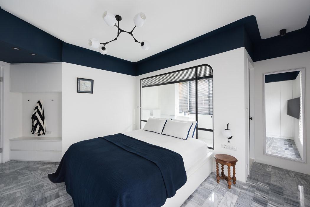 Groot raam met zwarte kozijnen tussen slaapkamer en badkamer