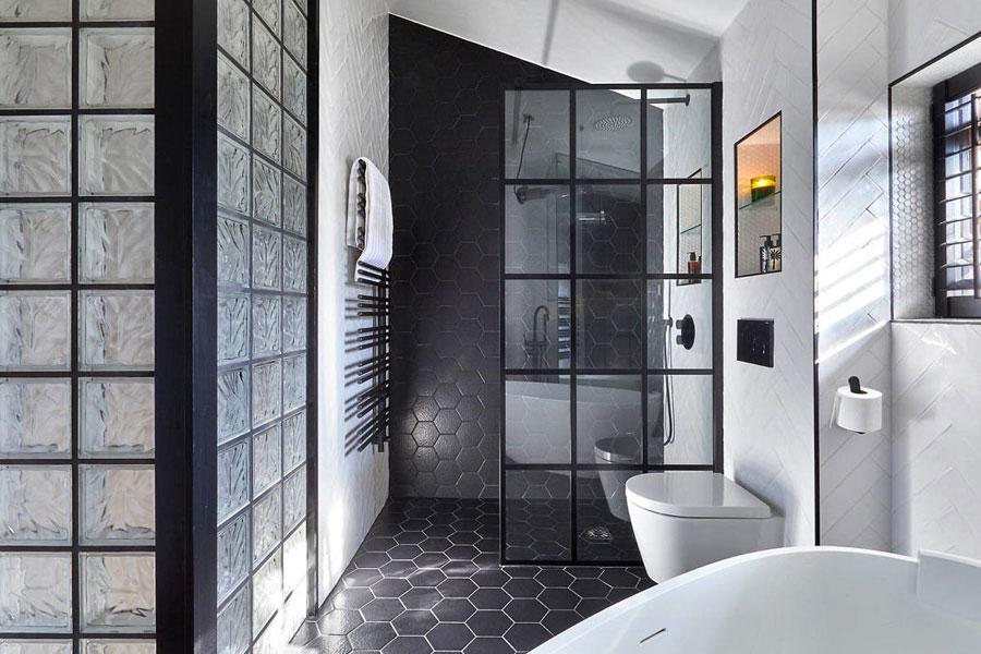 In deze moderne l-vormige badkamer is het strakke hangtoilet afgewerkt met visgraat wandtegels. Klik hier om meer foto's te bekijken.
