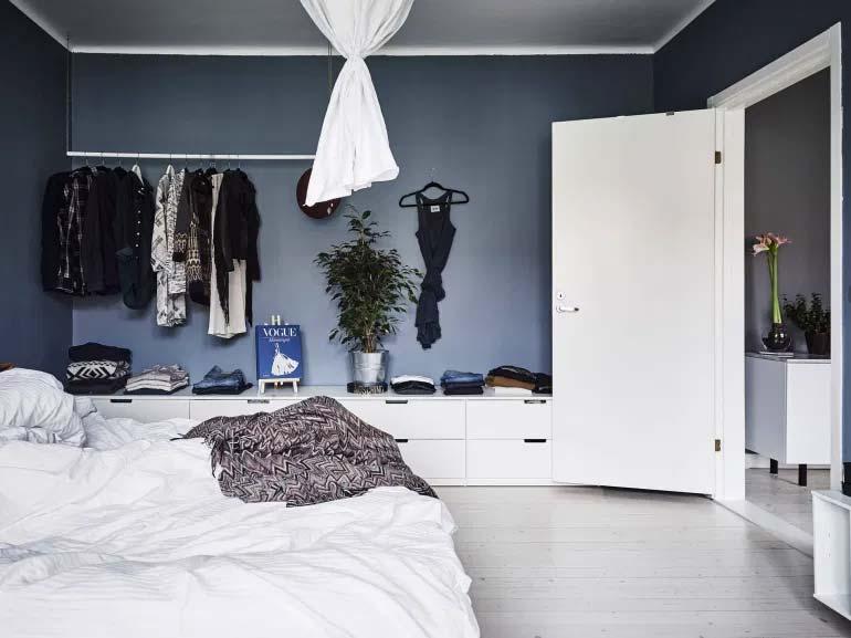 Open kledingkast met de Nordli ladekasten van IKEA in de slaapkamer met blauwe muren