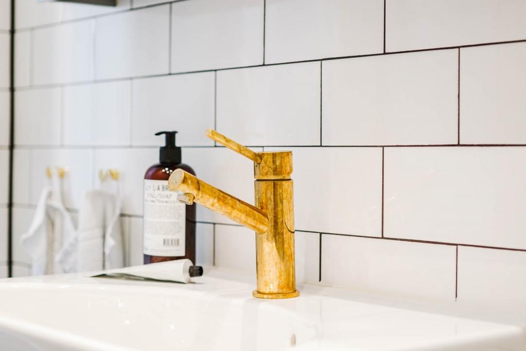 Deze kleine badkamer is afgewerkt met mooie gouden details