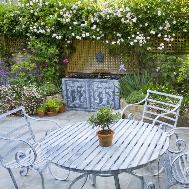 In deze kleine romantische tuin heeft Garden Club London gekozen voor een compacte maar erg stijlvolle waterval als focuspunt.