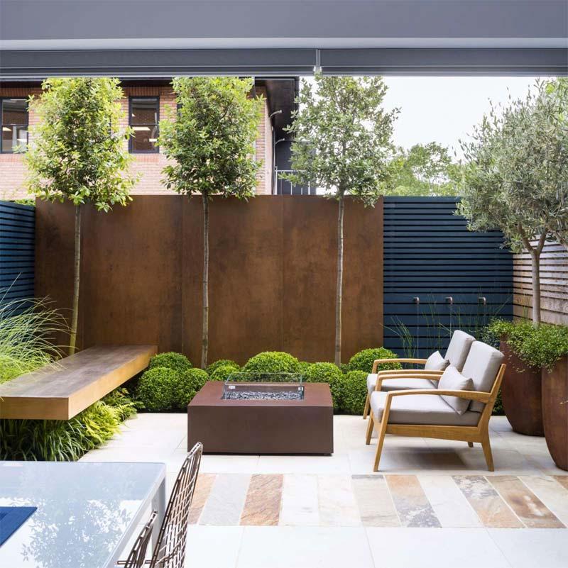 In deze moderne kleine tuin met tuintegels, en een mix van houten en cortenstalen schuttingen, heeft Garden Club London gekozen voor onder andere twee mooie olijfbomen in grote cortenstalen potten.