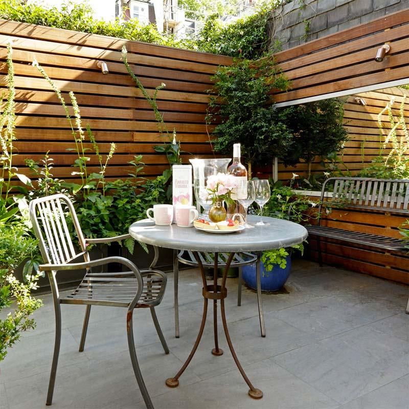 De grote spiegel op de houten schutting geeft deze kleine tuin het gevoel van extra ruimte.