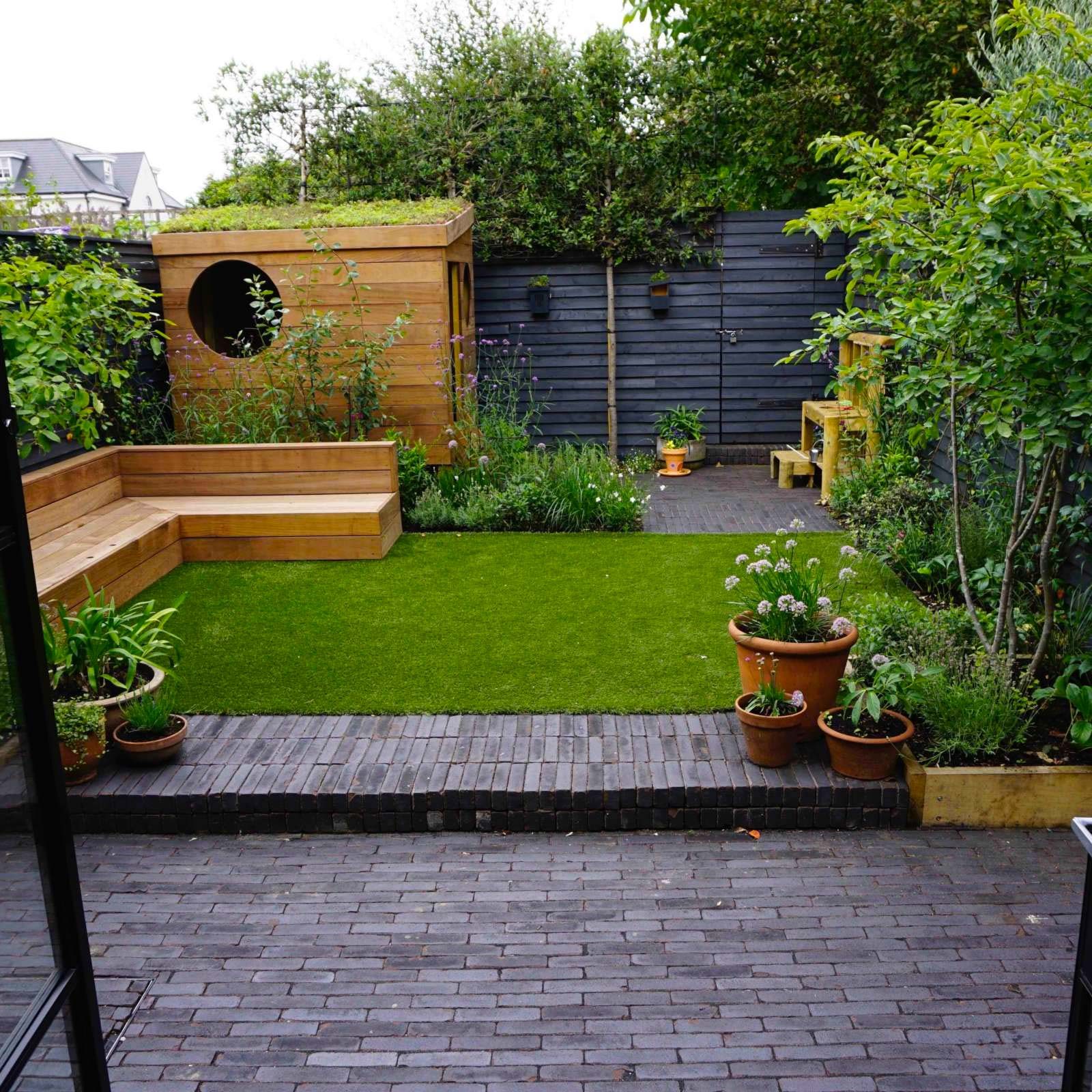 Garden Club Londen heeft in deze mooie kleine tuin gekozen voor een combinatie van klinkers, een groen gazon en zwarte houten schuttingen.