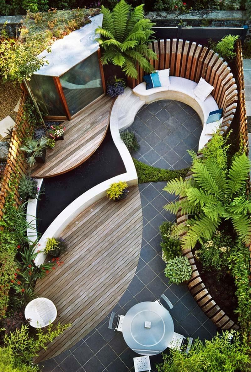 In deze rechthoekige moderne tuin zijn verschillende mooie ronde vormen gecreëerd met verhoogde borders, vlonders, een vijver en een ronde bank.