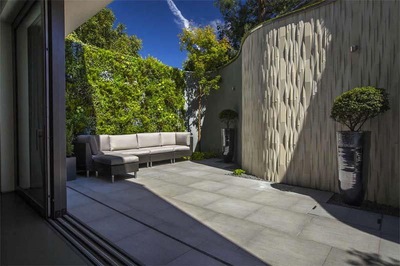 Garden Builders hebben deze kleine tuin ontworpen met een grote verticale tuin achter de loungebank.