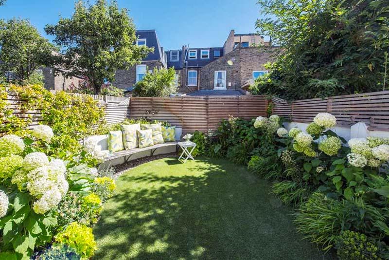 Kate Eyre Garden Design heeft in het meest zonnige hoekje van deze kleine tuin een heerlijke zithoek gecreëerd met een zwevende bank met kussens.