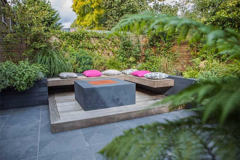 In deze kleine tuin heeft Garden Builders een knusse zithoek ingericht met een op maat gemaakte zwevende houten bank van hardhout ontworpen.
