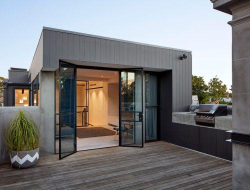 Modern dakterras met houten vlonders en betonstuc reling