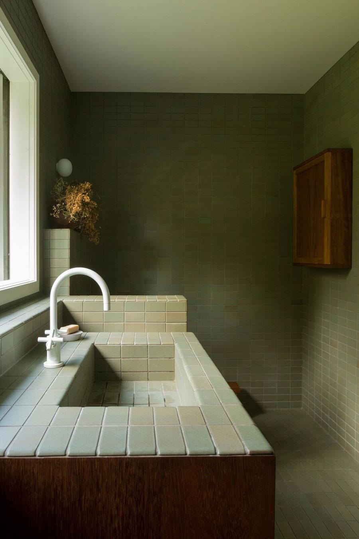Twee jaren '50 vintage stijl badkamers met mosgroene tegels