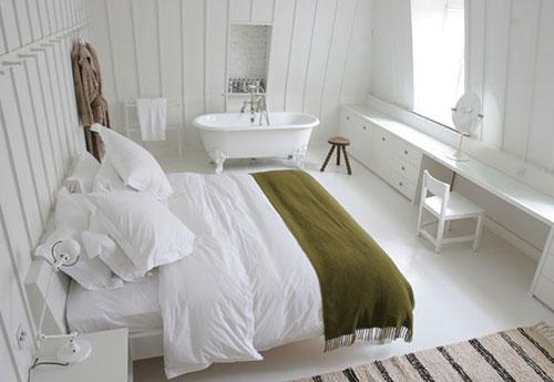 Witte slaapkamer met vrijstaand bad op pootjes