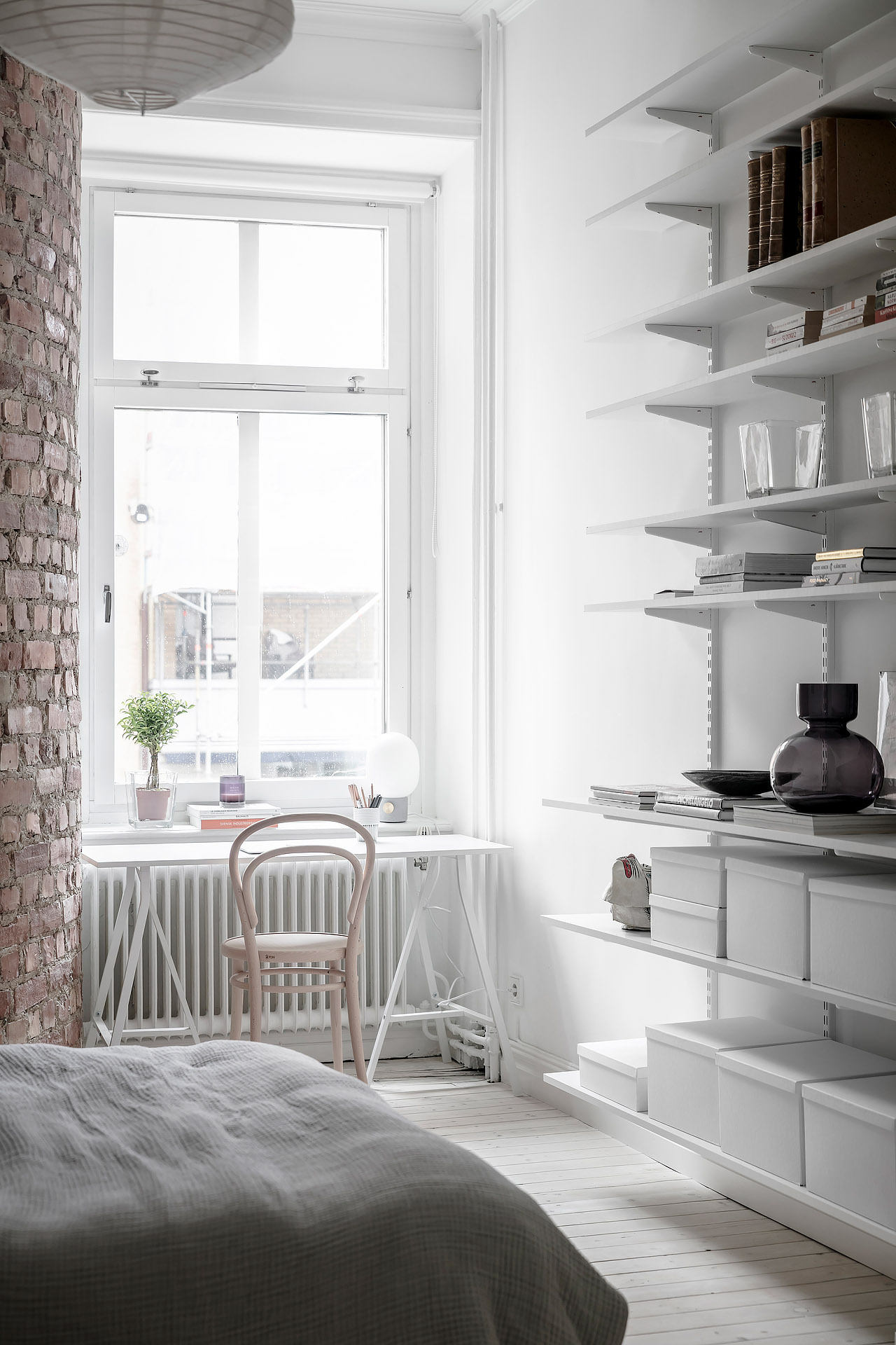 Deze witte slaapkamer is voorzien van een super charmante ronde bakstenen muur