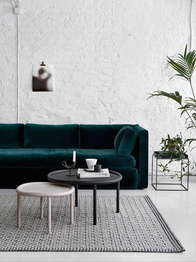 woonkamer ideeën - witte bakstenen muur en fluwelen groene bank
