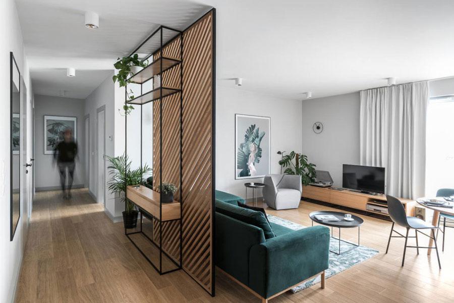woonkamer ideeen - mooie woonkamer met houten scheidingswand achter de groene bank