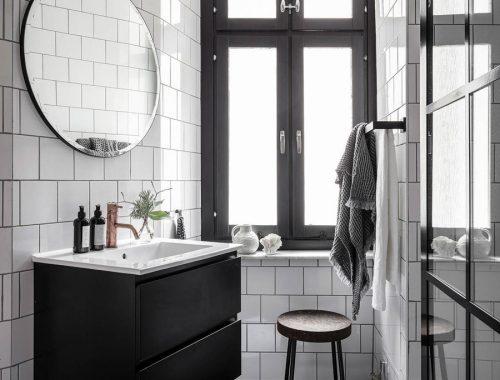Zwart wit badkamer met koperen details